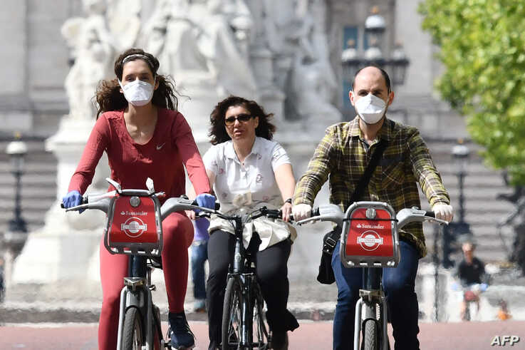 Cyclists, some wearing face masks, ride along The Mall near Buckingham Palace in central London, Britain, May 16, 2020, following an easing of coronavirus lockdown restrictions.