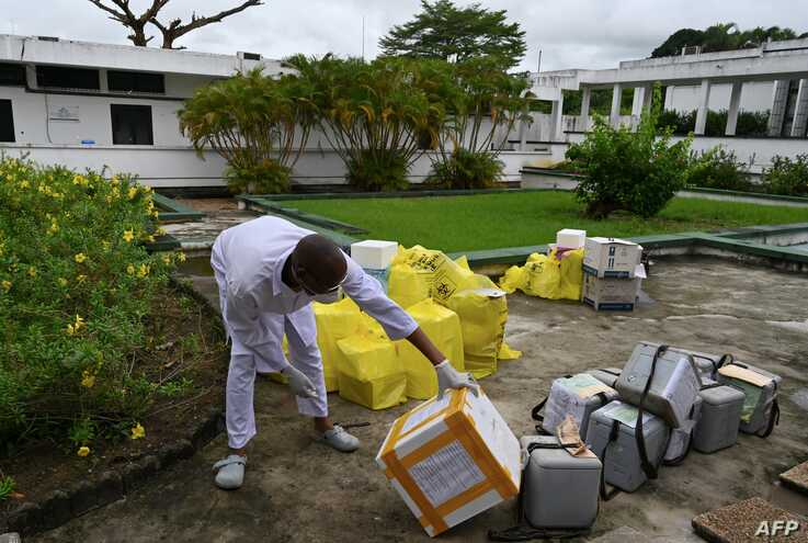 FILE - A lab technician at the Pasteur Institute of Ivory Coast looks at collected samples to be tested for the coronavirus and other samples for analysis, near Abidjan, May 11, 2020.