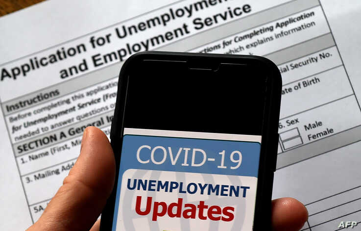 In this illustration photo taken May 08, 2020, a COVID-19 Unemployment Assistance Updates logo is displayed on a smartphone against the backdrop of an application for unemployment benefits, in Arlington, Virginia.