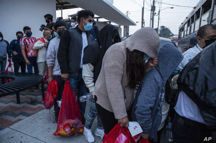 Guatemalans deported from the U.S., wearing masks as a precaution against the spread of the new coronavirus, board a bus after arriving at La Aurora airport in Guatemala City, May 4, 2020.