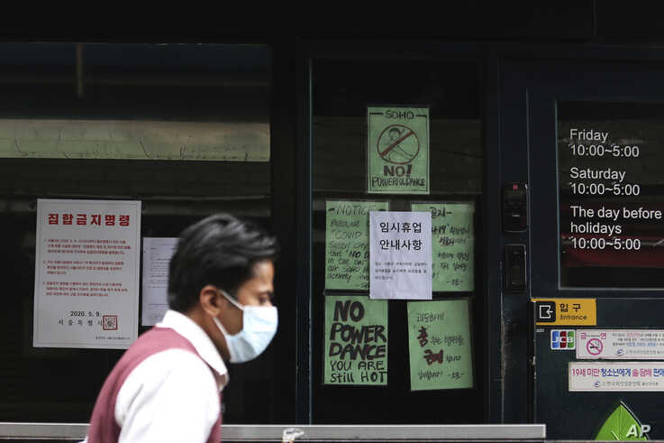 A man waring a face mask passes by the entrance of a temporary closed dance club in Seoul, South Korea, May 10, 2020.