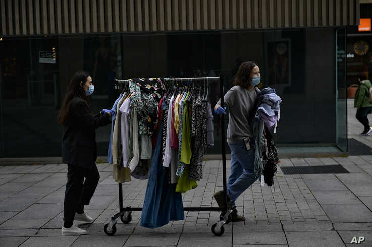 Two workers of clothes shop wearing face mask protections to prevent the spread of the coronavirus, pull a rack of clothes along a street, in Pamplona, northern Spain, May 11, 2020.