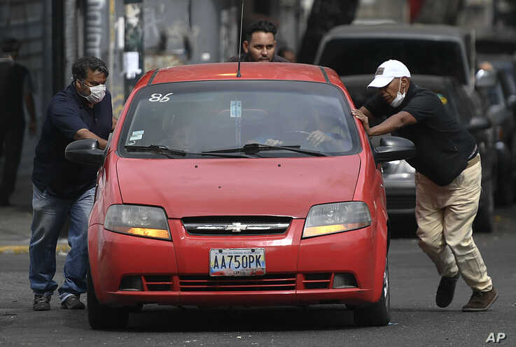 Men push a car that ran out of gas to a state-run oil company gas station, in Caracas, Venezuela, May 25, 2020.