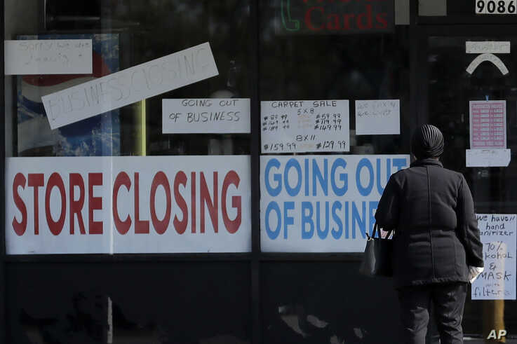FILE - A woman looks at signs at a store closed due to the coronavirus pandemic, in Niles, Illinois, May 13, 2020.