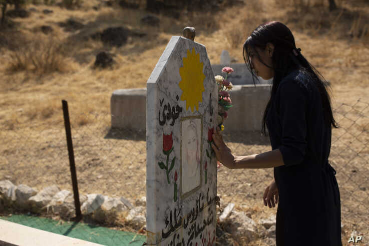 FILE - Layla Taloo visits the grave of a Yazidi woman who took her own life after she was captured by Islamic State militants in Mosul, buried on a hill overlooking the Lalish shrine in northern Iraq, Sept. 13, 2019.