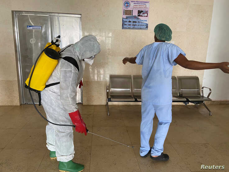 A health worker wearing protective equipment, disinfects a member of medical staff amid the spread of the coronavirus disease (COVID-19), at an hospital in Douala, Cameroon, April 27, 2020.