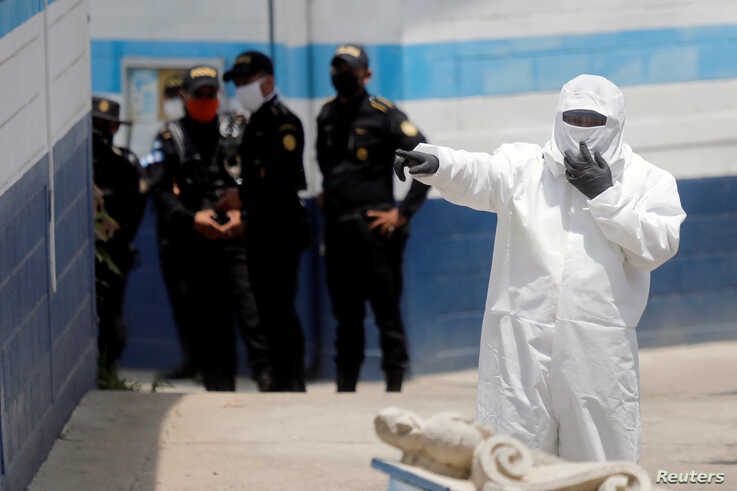 An employee of the Guatemala's Health Ministry, wearing a protective suit and a mask, gestures at a temporary shelter for Guatemalan migrants who arrived in the country on U.S. deportation flights, in Guatemala City, April 16, 2020.