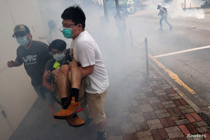 Anti-government protesters run away from tear gas during a march against Beijing's plans to impose national security legislation in Hong Kong, China, May 24, 2020.