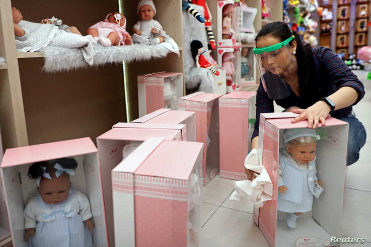 A woman disinfects merchandise at a doll store which reopened for business amid the coronavirus disease (COVID-19) outbreak in Madrid, Spain, May 19, 2020.