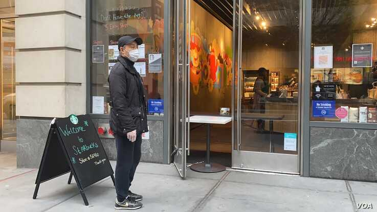 A man waits outside a Starbucks coffee shop at 34th street and 9th Ave. After weeks of not being open in this area, the coffee chain opened its doors with new social distancing measures. (Photo: Celia Mendoza / VOA)