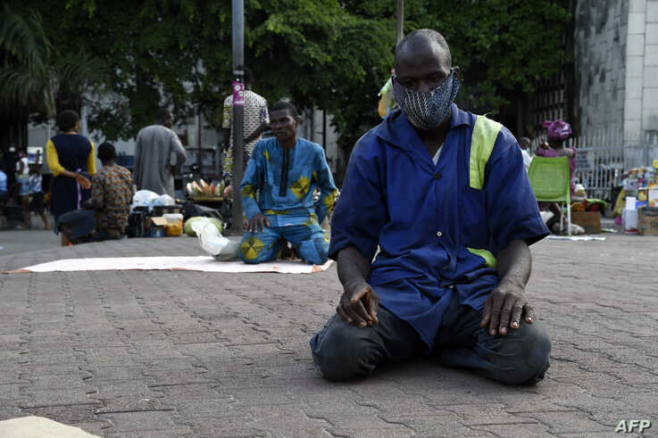 A Muslim man observes Ramadan prayers along the road in open space of Tinubu Square, wearing face masks and adhering to social…
