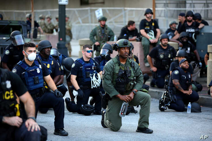 Officers kneel with protesters during a protest against the death in Minneapolis in police custody of African-American man George Floyd, in Downtown Atlanta, Georgia, U.S. June 1, 2020.