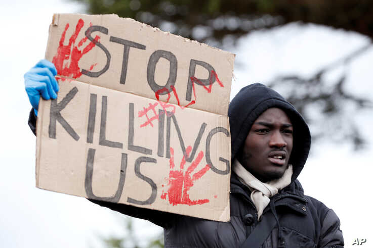 A demonstrator holds a placard during a Black Lives Matter protest in Watford, following the death of George Floyd who died in police custody in Minneapolis, Watford, Britain, June 6, 2020.