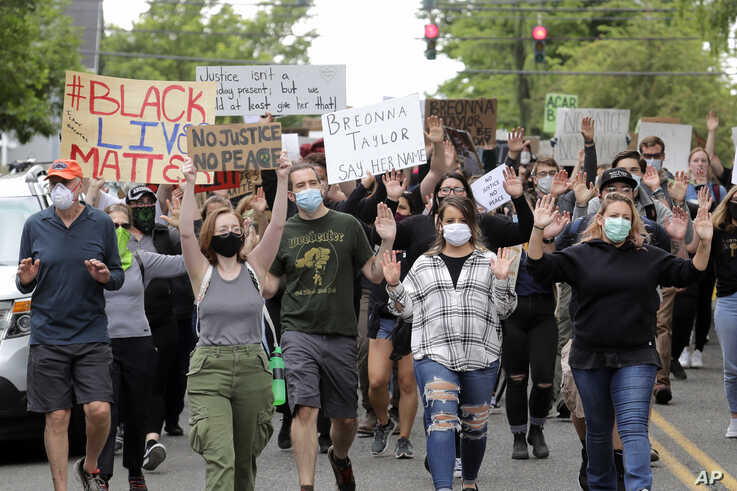 Protesters hold their hands up as they march near Wright Park, Friday, June 5, 2020, in Tacoma, Wash., during a protest against…