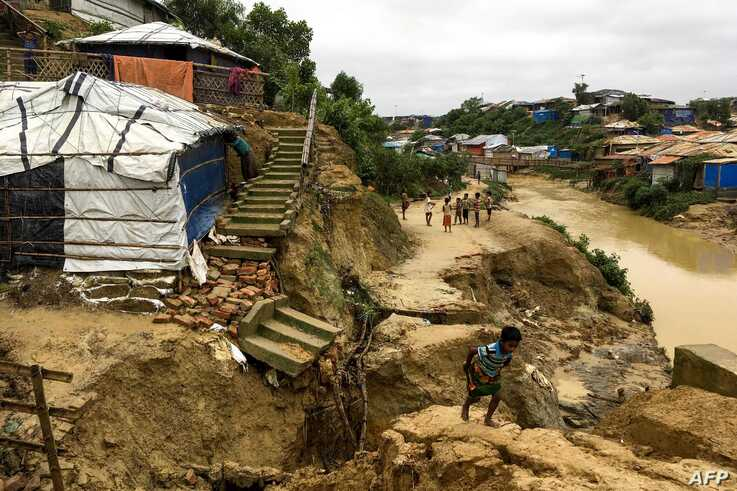 Rohingya children walk around a landslide area at Balukhali refugee camp in Ukhia, July 7, 2019. Monsoon-triggered landslides in Rohingya refugee camps in Bangladesh have killed one person and left more than 4,500 homeless, said officials said.