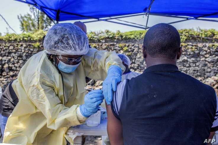 A man receives a vaccine against Ebola from a nurse outside the Afia Himbi Health Center on July 15, 2019 in Goma.  Authorities in Democratic Republic of Congo have appealed for calm after a preacher fell ill with Ebola in the eastern city of Goma,…