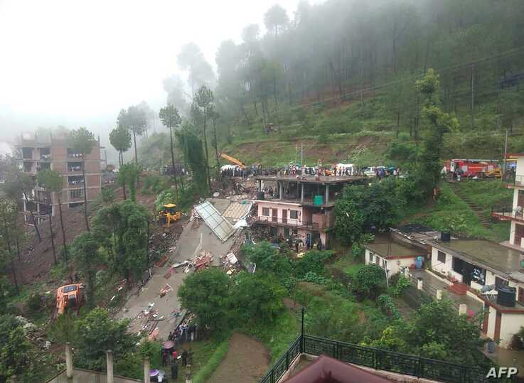 Indian rescuers work on a site after a multistory building collapsed following heavy rains near Kumarhatti, in Himachal Pradesh's Solan district.