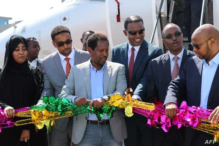 (FILES) In this file photo taken on October 13, 2018 the Mayor of Mogadishu, Abdirahman Omar Osman (3rd L), and CEO of Ethiopia's National Airways, Abera Lemi (3rd R), celebrate after the first commercial flight by National Airways linking Addis…