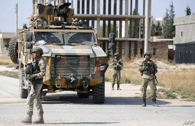 Turkish soldiers patrol the northern Syrian Kurdish town of Tal Abyad, on the border between Syria and Turkey, on October 23,…