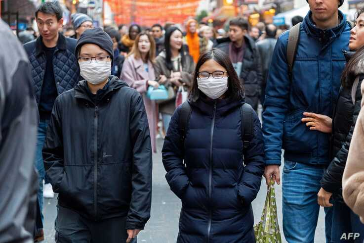 Pedestrians are seen wearing a surgical masks in London's China Town on January 25, 2020. - European airports from London to…