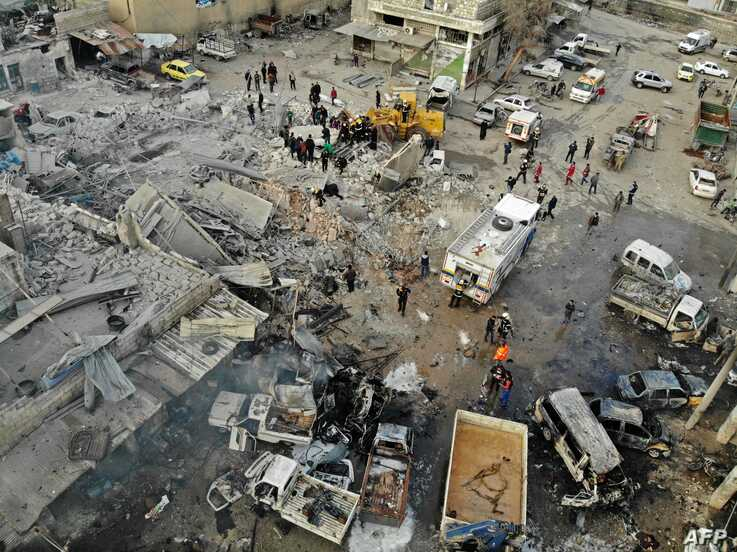 A drone picture taken on January 15, 2020, shows members of the Syrian Civil Defence, also known as the White Helmets,…