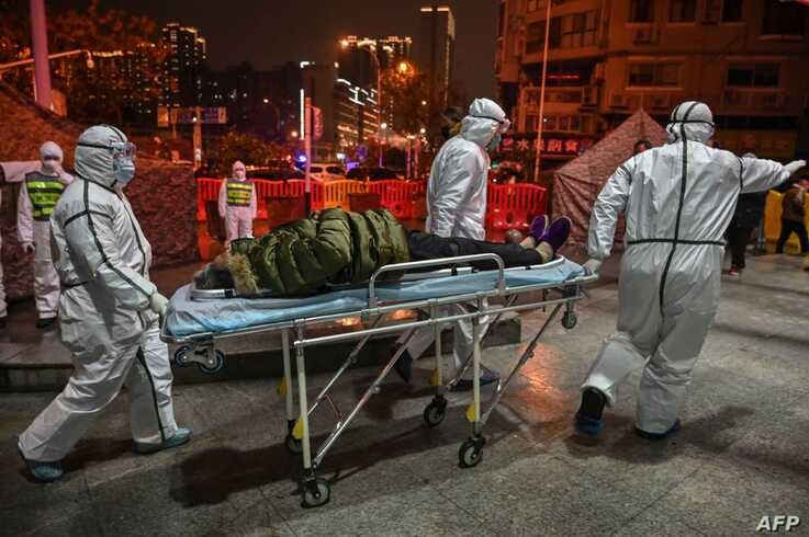 TOPSHOT - Medical staff members wearing protective clothing to help stop the spread of a deadly virus which began in the city,…