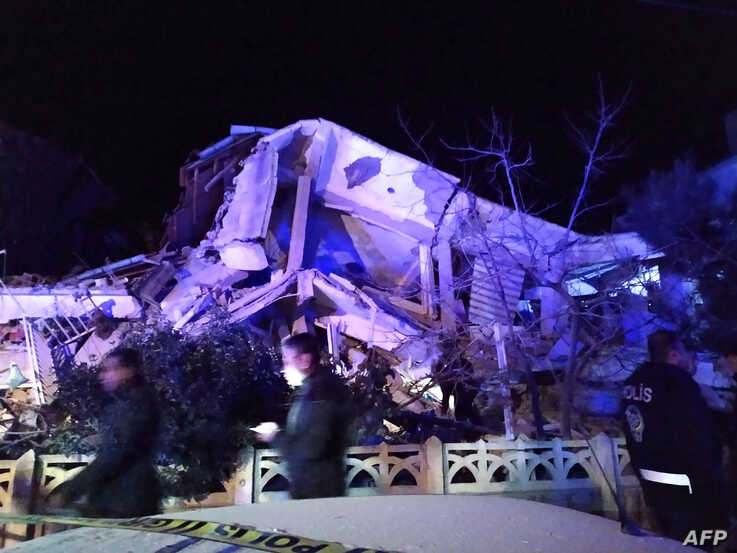 Turkish officials and police arrive at the scene of a collapsed building following a 6.8 magnitude earthquake in Elazig,…