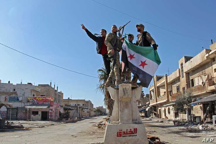TOPSHOT - Turkey-backed Syrian fighters celebrate in the town of Saraqib in the eastern part of the Idlib province in…
