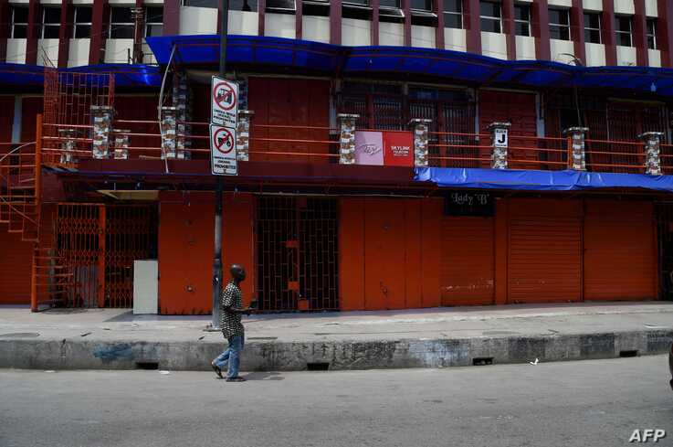 A man walk past a closed shop in compliance with a seven-day partial shutdown by the state government to combat the spread of…
