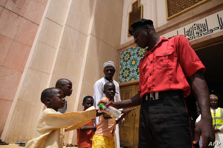 A security official dispenses hand sanitizer to worshippers at the National Mosque in Abuja, Nigeria, on March 20, 2020. -…