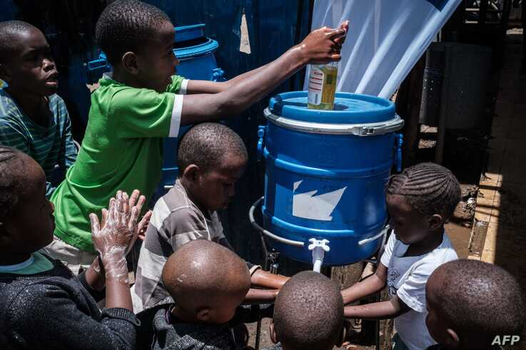 Children learn how to wash hands for prevention of the COVID-19 as local NGO Shining Hope for Communities (SHOFCO) installs…