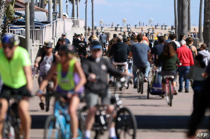 HUNTINGTON BEACH, - MARCH 21: People ride their bikes along a bike bath near the pier on March 21, 2020 in Huntington Beach,…
