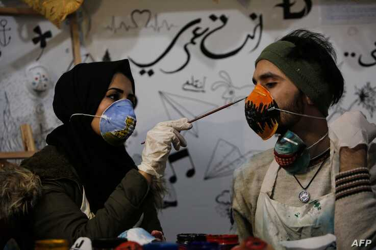 Palestinian artist Samah Said (L) paints an N95 protective mask worn by fellow artist Dorgham Krakeh (R) for a project raising…