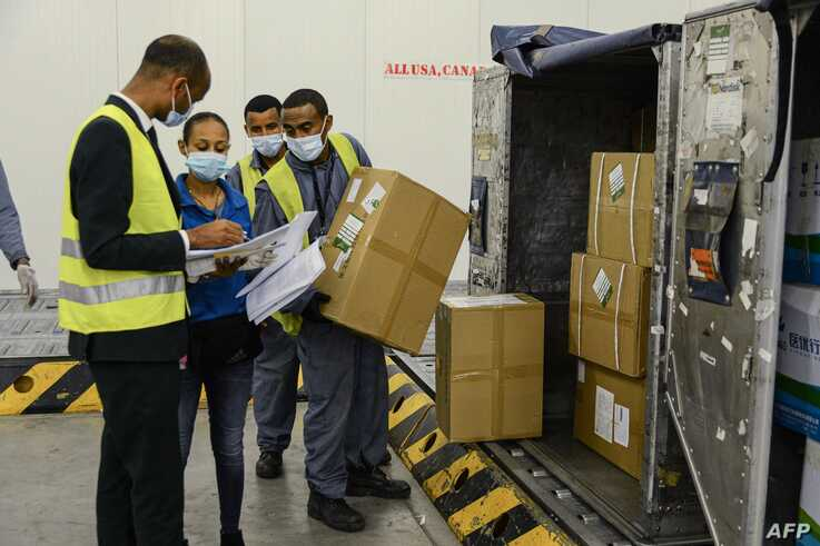 Staff of the World Food Programme (WFP) check boxes that arrived, mostly personal protective equipment (PPE), at Ethiopian…