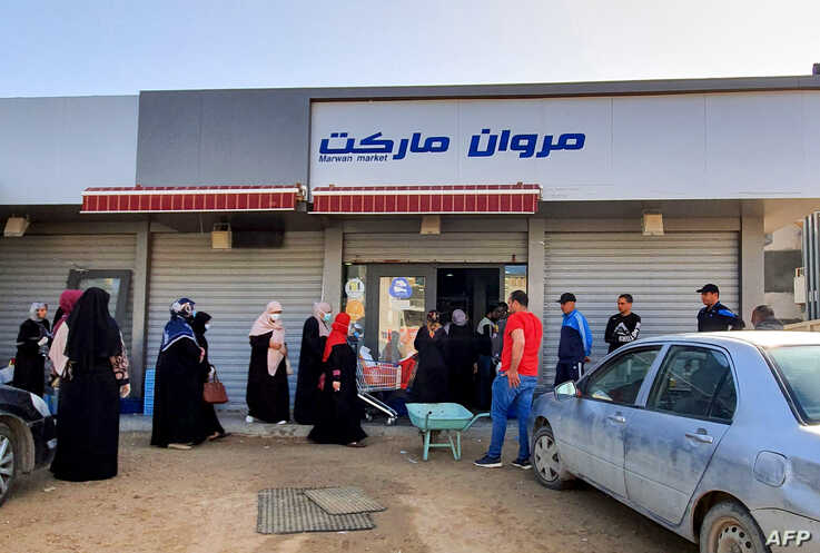 Libyans queue outside a super market, during a curfew announced by the UN-recognised Government of National Accord (GNA) in…