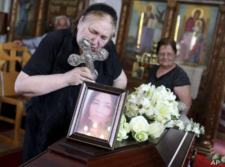 The mother of Livia Florentina Bunea leans over to kiss a cross during the funeral of Livia Florentian Bunea, 36, from Romania and her eight year-old daughter Elena Natalia at a church in the village of Arediou, southwest of Cyprus' capital Nicosia…