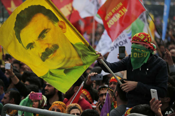 A youth holds a flag with the image of Abdullah Ocalan, the jailed leader of the rebel Kurdistan Workers' Party, or PKK, during the Newroz celebrations, marking the start of spring, in Istanbul, Wednesday, March 21, 2018. Thousands celebrated the…
