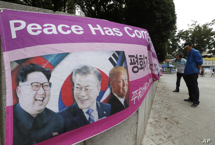A banner shows images, from left, of North Korean leader Kim Jong Un, South Korean President Moon Jae-in and U.S. President Donald Trump, displayed by protesters who demand the peace on the Korean peninsula near U.S. Embassy in Seoul, South Korea,…