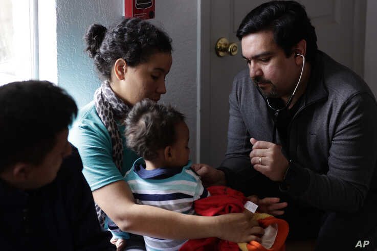 Dr. Martin Garza, right, a pediatrician who volunteers at Catholic Charities in McAllen, Texas, checks migrant families just released from immigration detention, March 15, 2019.