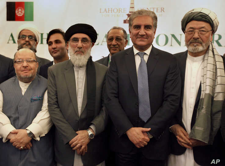 Afghan politicians and other participants pose with Pakistani Foreign Minister Shah Mahmood Qureshi, second right, after the opening session of an Afghan Peace Conference in Bhurban, Pakistan,  June 22, 2019.