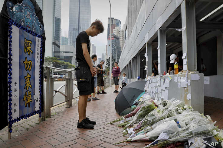 A man pays respect on the site where a man fell to his death a day earlier after hanging a protest banner against the extradition bill on the scaffolding of a shopping mall in Hong Kong, Sunday, June 16, 2019. Hong Kong was bracing Sunday for…