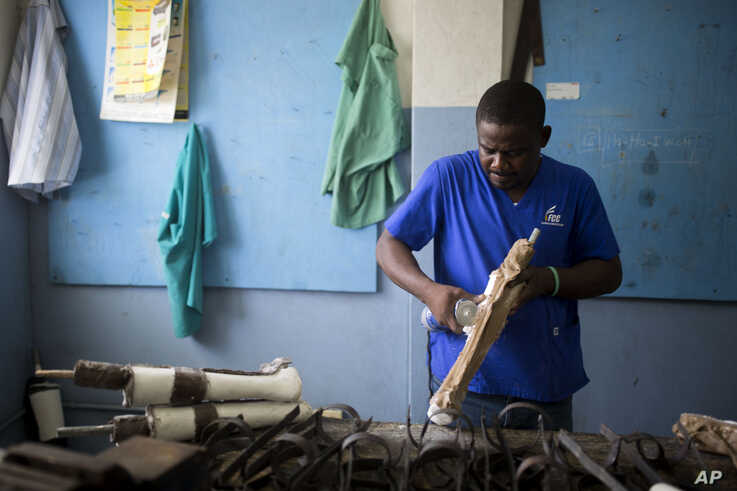 In this June 4, 2019 photo, prosthetic technician Wilfrid Macena works in a workshop at the St. Vincent's Center, an institution run by Haiti's Episcopal Church in downtown Port-au-Prince, where a small group of disabled workers fit those who have…