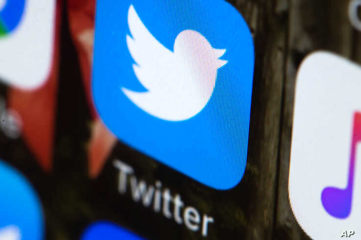 FILE - This April 26, 2017, file photo shows the Twitter app on a mobile phone in Philadelphia.  Twitter will now prohibit hate speech that targets religious groups using dehumanizing language. The social network already bans hateful language…