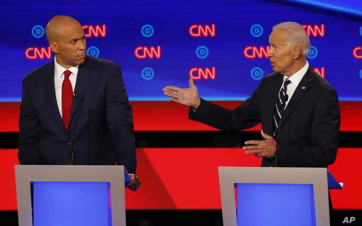 Sen. Cory Booker, D-N.J., listens as former Vice President Joe Biden speaks during the second of two Democratic presidential primary debates hosted by CNN, July 31, 2019, in the Fox Theatre in Detroit.