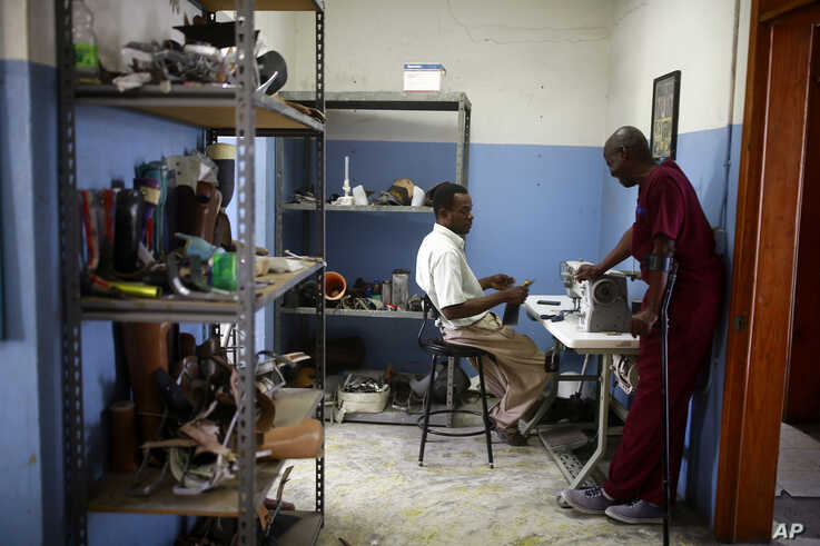 In this May 22, 2019 photo, technicians Cereste Cherisme, right, and Jules Emmanuel, chat during their shift at the workshop in St. Vincent's Center in Port-au-Prince, Haiti. The workshop is run by Haiti's Episcopal Church in downtown Port-au-Prince…