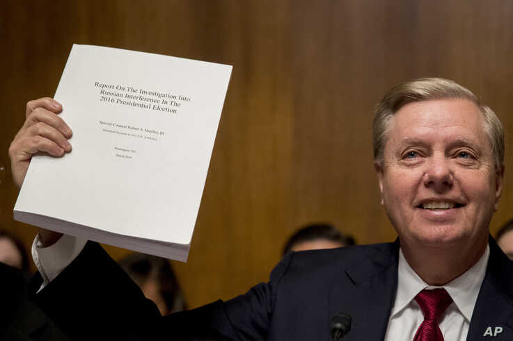 Chairman Sen. Lindsey Graham, R-S.C., holds up a copy of the Mueller Report during a Senate Judiciary Committee hearing on Capitol Hill in Washington, Wednesday, May 1, 2019, where Attorney General William Barr testifies on the Mueller Report. (AP…