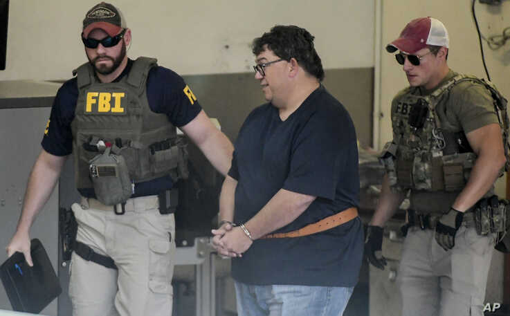 FBI agents escort businessman Fernando Scherrer-Caillet who was arrested in San Juan, Puerto Rico, Wednesday, July 10, 2019. Puerto Rico's former secretary of education and four other people including  Scherrer-Caillet have been arrested on charges…