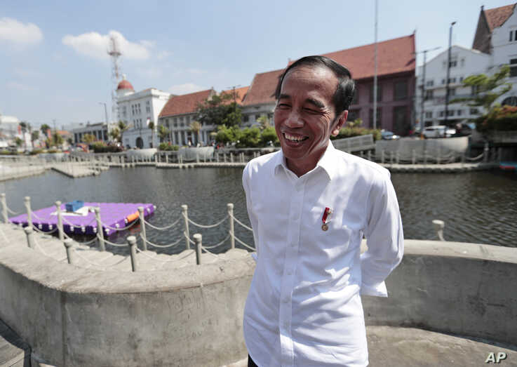 Indonesian President Joko Widodo smiles as he talks to The Associated Press during his visit at the newly revitalized 18th century Kali Besar Canal at the Old Town in Jakarta, Indonesia, July 26, 2019.