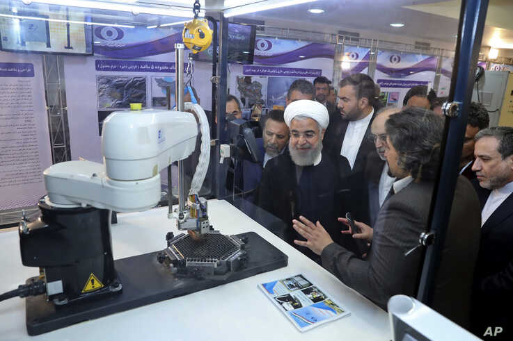 FILE - President Hassan Rouhani listens to explanations of  nuclear achievements in Tehran, Iran, April 9, 2018. Iran has broken the limit set on its stockpile of low-enriched uranium by the 2015 nuclear deal, and will raise its enrichment of uranium.