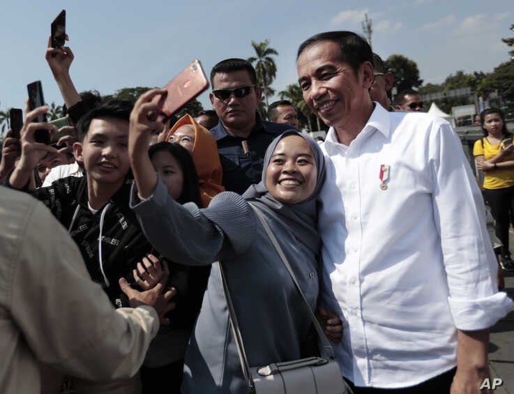 A Muslim woman takes a selfie with Indonesian President Joko Widodo, right, during his visit at the Old Town in Jakarta, Indonesia, July 26, 2019.